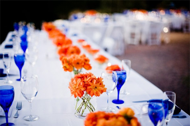 Table centerpieces, made of wicker decorative balls, tea candles, pine cones, glass beads and beach pebbles in black and white, golden and brown colors, combined with fabric napkins and flowers, like daisies and marigolds, in orange color shades evocative of fall leaf colors, create versatile table decorations for fall holidays.
